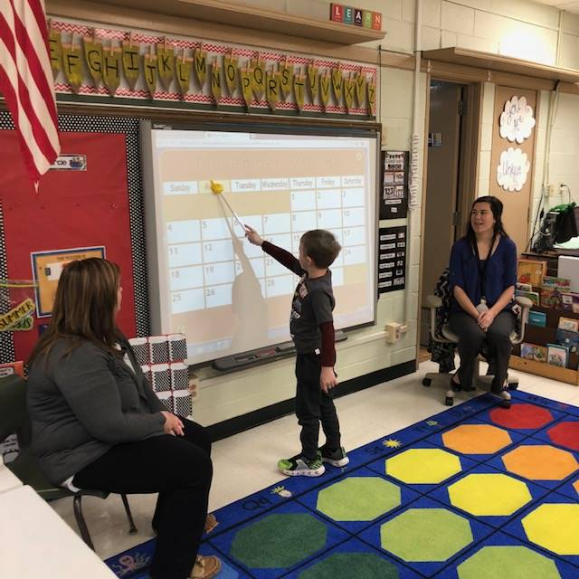 Student participating in calendar activity on smartboard